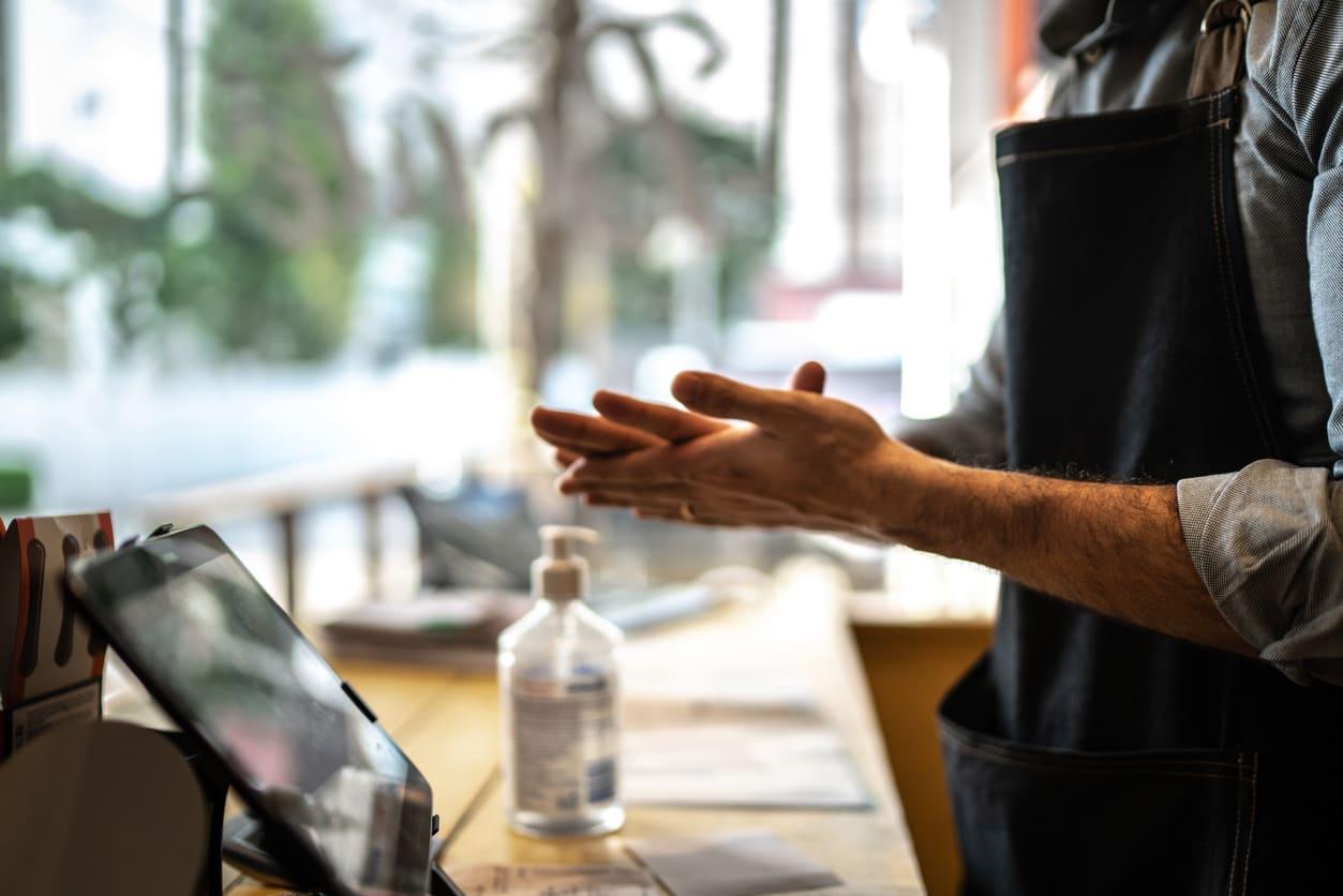 Cajero usando gel hidroalcoholico | Cofidis Retail